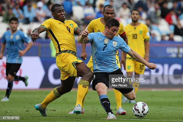 Cristian Rodriguez of Uruguay fights for the ball with Wes Morgan of Jamaica during the 2015 Copa America Chile Group B match between Uruguay and...