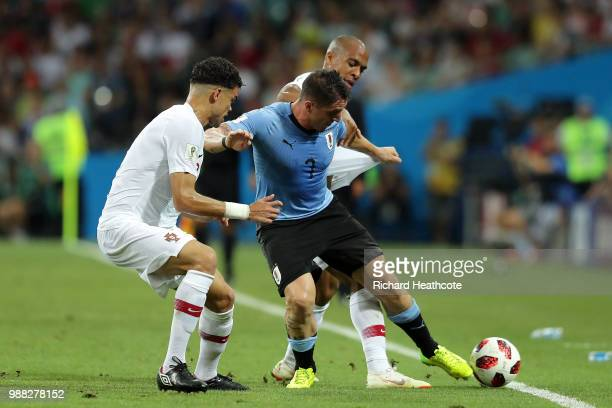 Cristian Rodriguez of Uruguay is challenged by Joao Mario and Pepe of Portugal during the 2018 FIFA World Cup Russia Round of 16 match between...