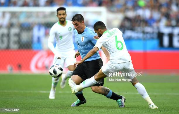 Cristian Rodriguez of Uruguay is tackled by Mohammed Alburayk of Saudi Arabia during the 2018 FIFA World Cup Russia group A match between Uruguay and...