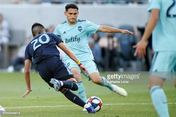 Cristian Roldan of Seattle Sounders prepares to kick the ball away while Eduard Atuesta of Los Angeles FC moves in during a game at Banc of...