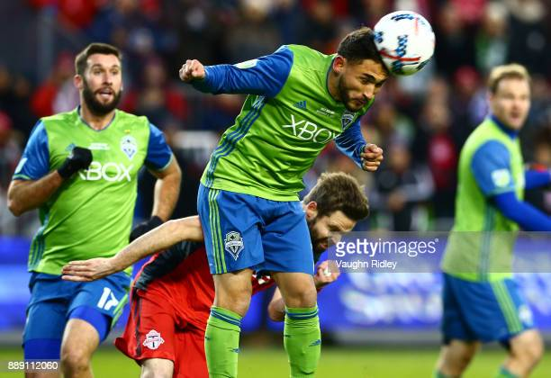 Cristian Roldan of the Seattle Sounders wins a header against Drew Moor of Toronto FC during the first half of the 2017 MLS Cup Final at BMO Field on...
