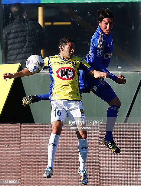 Cristian Suarez of U de Chile fights for the ball with Hector Berrios of U de Concepcion during a match between U de Chile and U de Concepcion as...