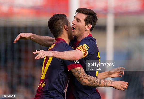 Cristian Tello of FC Barcelona celebrsates with teammate Lionel Messi after scoring his team's first goal during the La Liga match between RC Celta...