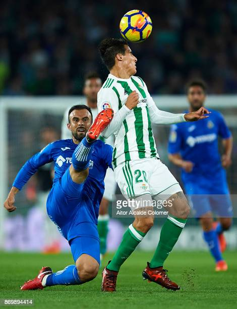 Cristian Tello of Real Betis Balompie competes for the ball with Francisco Molinero of Getafe CF during the La Liga match between Real Betis and...