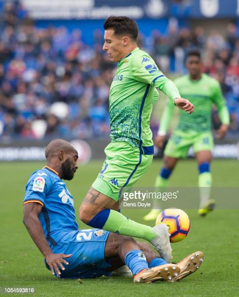 Cristian Tello of Real Betis Balompie is tackled by Dimitri Foulquier of Getafe during the La Liga match between Getafe CF and Real Betis Balompie at...