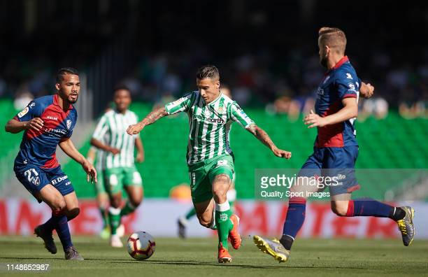Cristian Tello of Real Betis competes for the ball with Herrera of SD Huesca during the La Liga match between Real Betis Balompie and SD Huesca at...