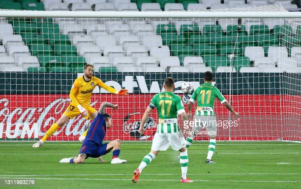 Cristian Tello of Real Betis scores their side's first goal past Jan Oblak of Atletico de Madrid during the La Liga Santander match between Real...