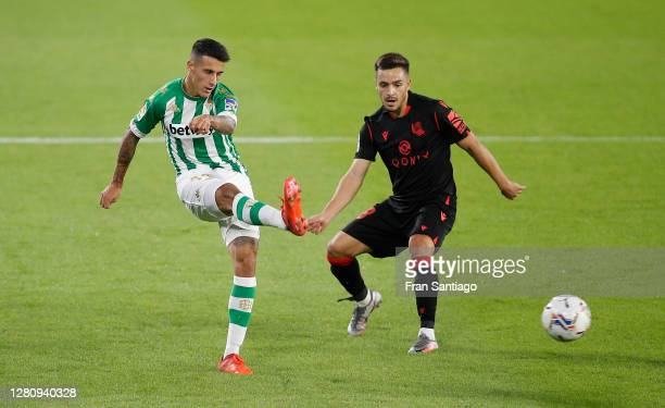 Cristian Tello of Real Betis shoots past Andoni Gorosabel of Real Sociedad during the La Liga Santander match between Real Betis and Real Sociedad at...