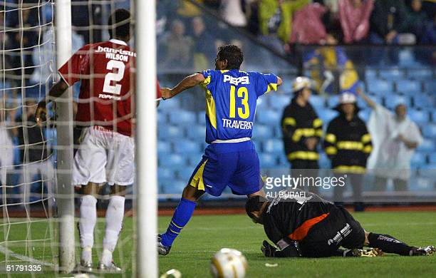 Cristian Traverso of Boca Juniors of Argentina celebrates between goalkeeper Clemer and defender Wilson after scoring the first goal against...