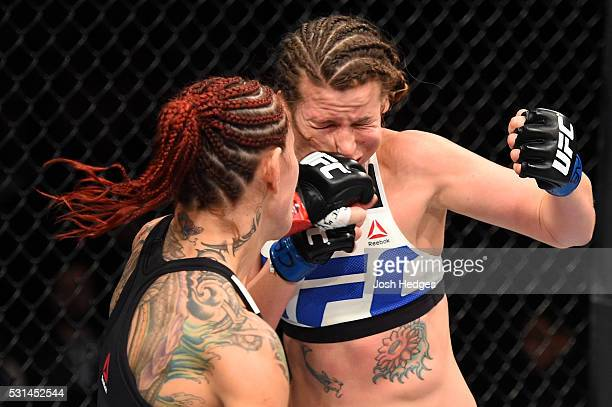 Cristiane 'Cyborg' Justino of Brazil punches Leslie Smith in their women's catchweight bout during the UFC 198 event at Arena da Baixada stadium on...