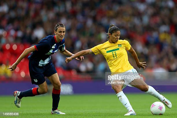 Cristiane of Brazil shoots at goal under pressure from Jill Scott of Great Britain during the Women's Football first round Group E Match between...