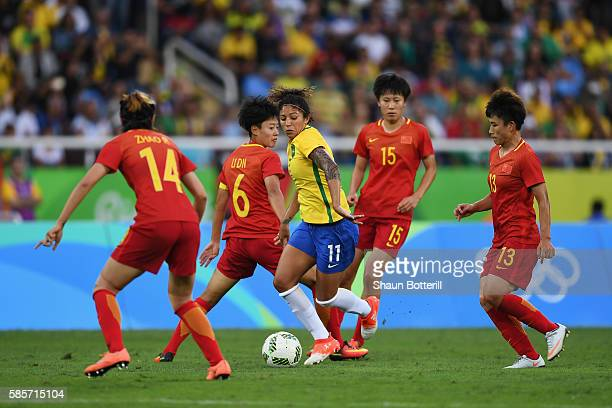 Cristiane of Brazil takes on Rong Zhao Dongna Li Rui Zhang and Fengyue Pang of China during the Women's Group E first round match between Brazil and...