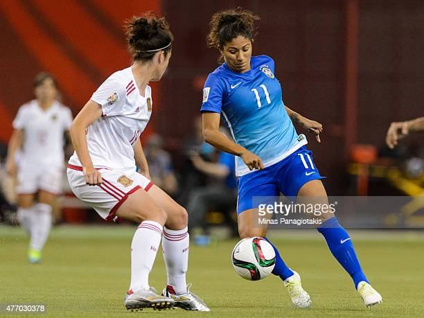 Cristiane of Brazil tries to get the ball past Marta Torrejon of Spain during the 2015 FIFA Women's World Cup Group E match at Olympic Stadium on...