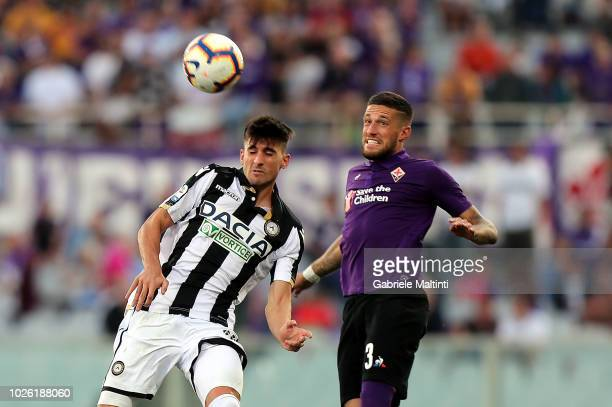 Cristiano Biraghi of ACF Fiorentina battles for the ball with Ignacio Pussetto of Udinese Calcio during the serie A match between ACF Fiorentina and...