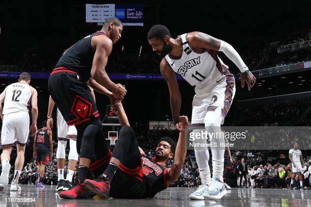 Cristiano Felicio of the Chicago Bulls and Kyrie Irving of the Brooklyn Nets helps up Chandler Hutchison of the Chicago Bulls on January 31 2020 at...