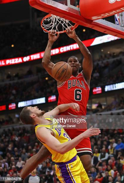 Cristiano Felicio of the Chicago Bulls dunks over Mike Muscala of the Los Angeles Lakers at the United Center on March 12 2019 in Chicago Illinois...