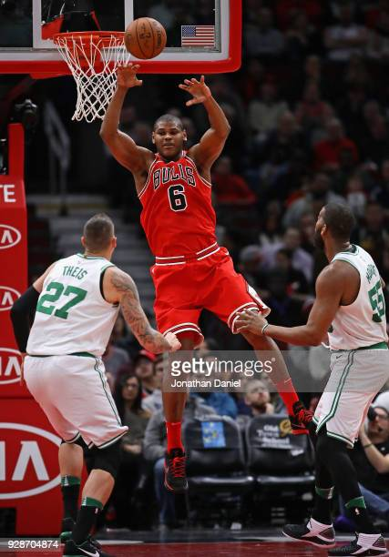 Cristiano Felicio of the Chicago Bulls leaps to pass over Daniel Theis and Greg Monroe of the Boston Celtics at the United Center on March 5 2018 in...