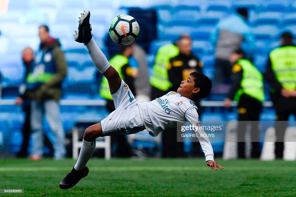 Cristiano Jr, son of Real Madrid's Portuguese forward Cristiano Ronaldo, kicks a ball at the end of the Spanish league football match between Real Madrid CF and Club Atletico de Madrid at the Santiago Bernabeu stadium in Madrid on April 8, 2018. /