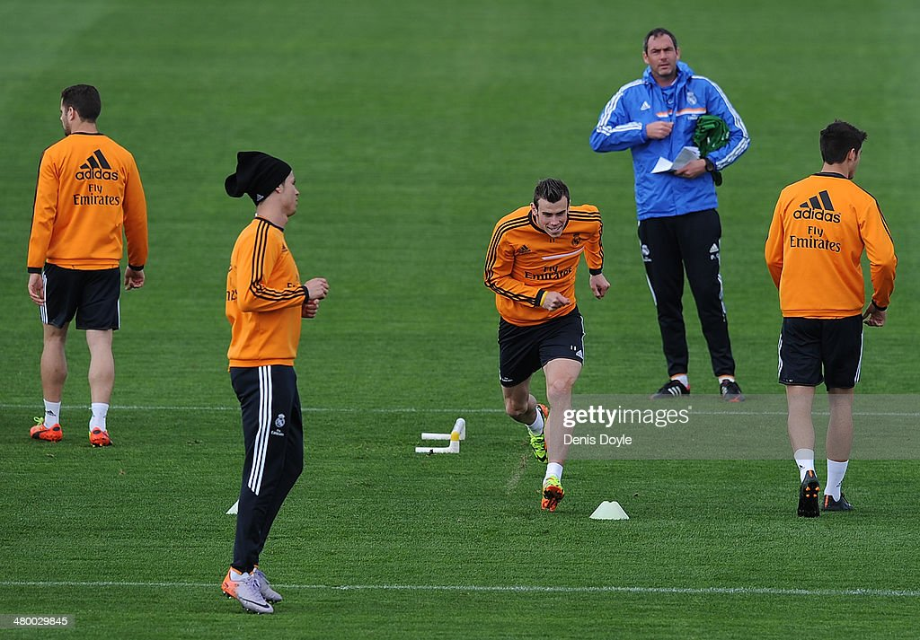 Cristiano Ronaldo (2.L) and Gareth Bale (C) of Real Madrid CF warm up while assistant coach Paul Clement (2.R) looks on during a team training session ahead of their El Clasico match against Barcelona at Valdebebas training ground on March 22, 2014 in Madrid, Spain.