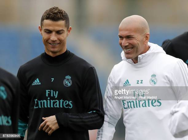 Cristiano Ronaldo and head coach Zinedine Zidane of Real Madrid smile during a training session at Valdebebas training ground on November 24 2017 in...