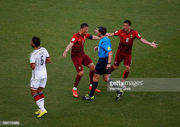 Cristiano Ronaldo and Joao Moutinho of Portugal react toward referee Milorad Mazic during the 2014 FIFA World Cup Brazil Group G match between...