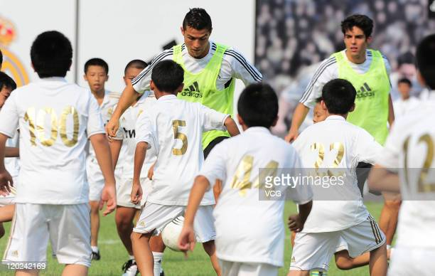 Cristiano Ronaldo and Kaka of Real Madrid play with children of Guangzhou Real Madrid Foundation Football School during a training session at Tianhe...