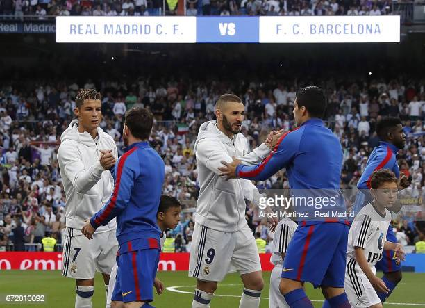 Cristiano Ronaldo and Karim Benzema of Real Madrid greet Lionel Messi and Luis Suarez of FC Barcelona prior to the La Liga match between Real Madrid...
