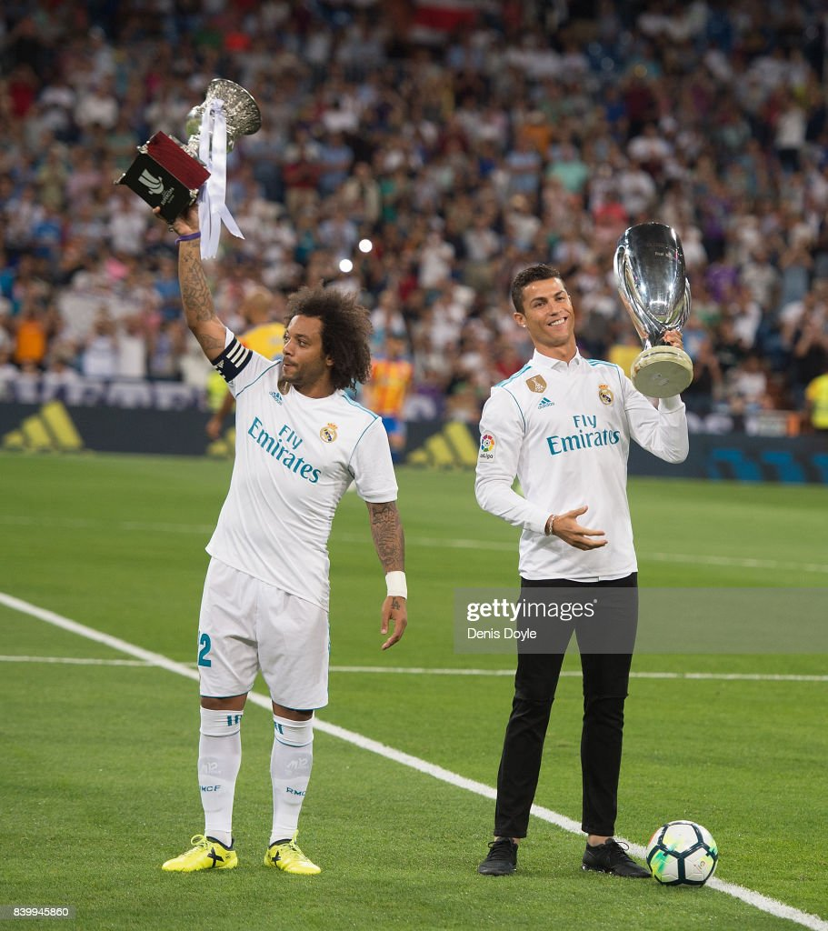 Cristiano Ronaldo and Marcelo of Real Madrid CF hold up the UEFA Super Cup (right) and LaLiga title for 2016/2017 before the La Liga match between Real Madrid CF and Valencia CF at Estadio Santiago Bernabeu on August 27, 2017 in Madrid, Spain .