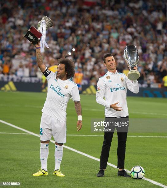Cristiano Ronaldo and Marcelo of Real Madrid CF hold up the UEFA Super Cup and LaLiga title for 2016/2017 before the La Liga match between Real...