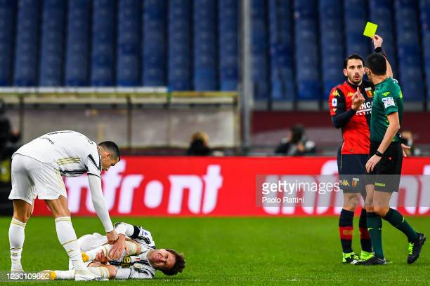 Cristiano Ronaldo checks Federico Chiesa of Juventus conditions as referee Marco Di Bello shows Edoardo Goldaniga of Genoa a yellow card during the...