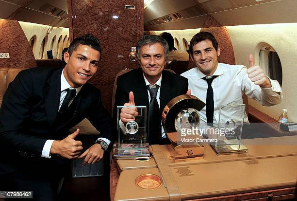 Cristiano Ronaldo head coach Jose Mourinho and Iker Casillas of Real Madrid pose with their trophies during their flight back after the FIFA Ballon...