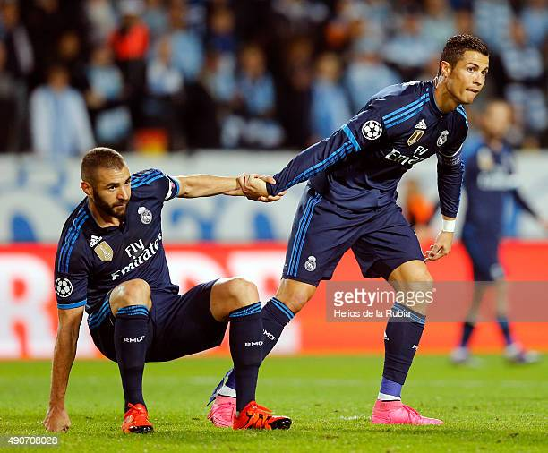 Cristiano Ronaldo helps her up a Karim Benzema of Real Madrid during the UEFA Champions League Group A match between Malmo fc and Real Madrid CF at...