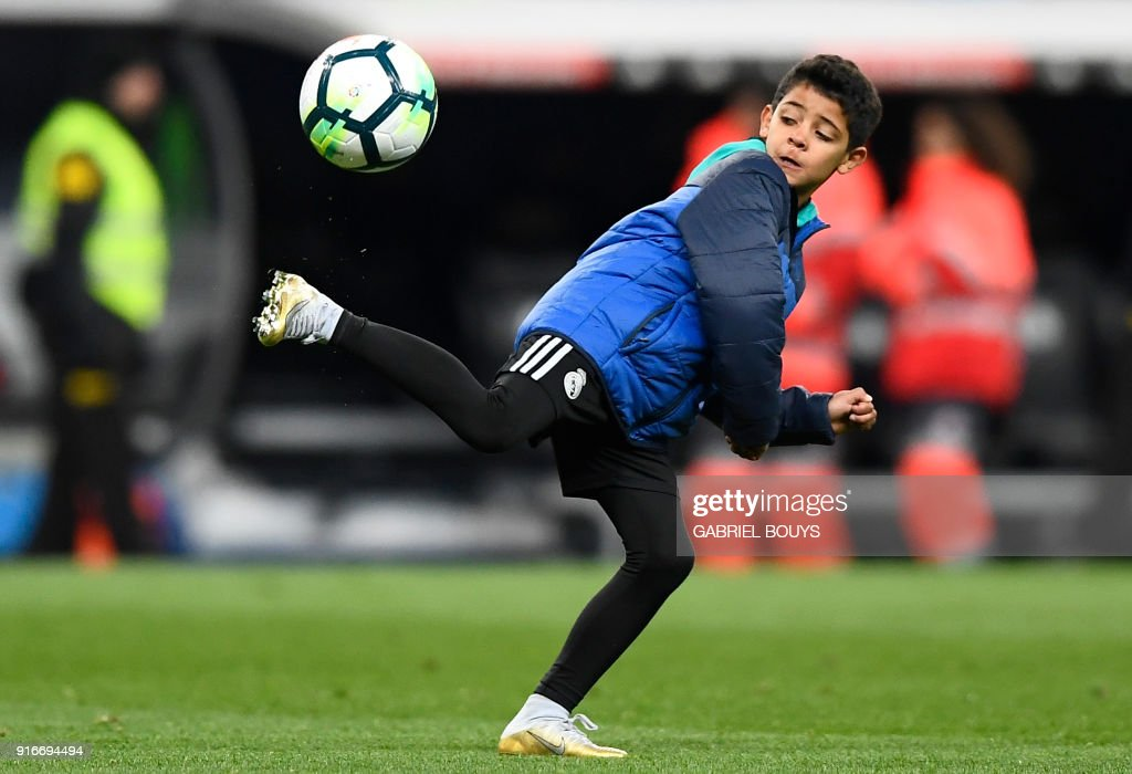 TOPSHOT - Cristiano Ronaldo Jr, son of Real Madrid's Portuguese forward Cristiano Ronaldo, plays with a ball after the Spanish league football match between Real Madrid CF and Real Sociedad at the Santiago Bernabeu stadium in Madrid on February 10, 2018. /