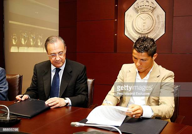 Cristiano Ronaldo next the President of Real Madrid Florentino Perez sign his contract before his official presentation as new Real Madrid Player at...