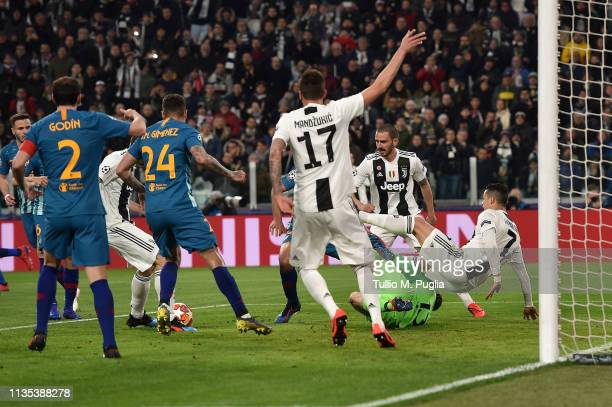 Cristiano Ronaldo of Juventus and Jan Oblak of Atletico Madrid ccompete for the ball during the UEFA Champions League Round of 16 Second Leg match...