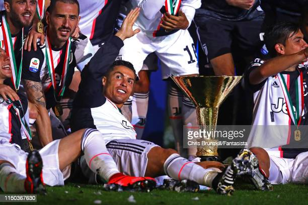 Cristiano Ronaldo of Juventus celebrates alongside the Serie A trophy following the Serie A match between Juventus and Atalanta BC at Allianz Stadium...