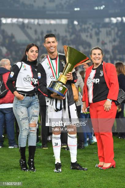 Cristiano Ronaldo of Juventus celebrates with his mother Maria Dolores Aveiro and Georgina Rodriguez during the awards ceremony after winning the...