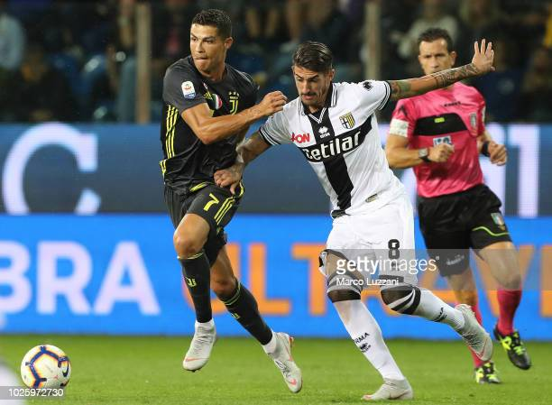 Cristiano Ronaldo of Juventus competes for the ball with Alessandro Deiola of Parma Calcio during the serie A match between Parma Calcio and Juventus...