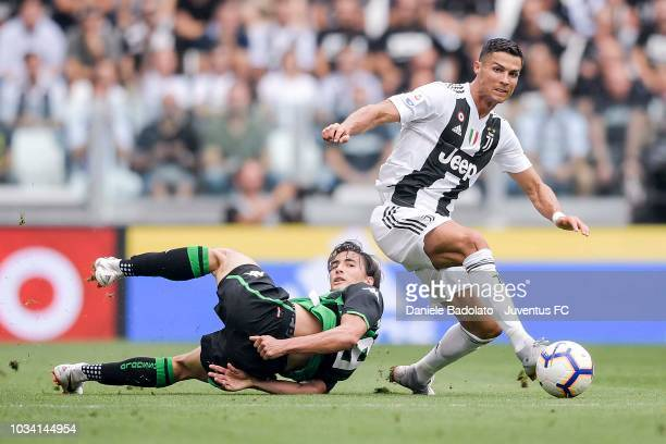 Cristiano Ronaldo of Juventus competes for the ball with Filip Djuricic of US Sassuolo during the serie A match between Juventus and US Sassuolo at...
