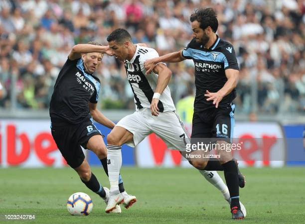 Cristiano Ronaldo of Juventus competes for the ball with Lucas Leiva Pezzini and Marco Parolo of SS Lazio during the Serie A match between Juventus...