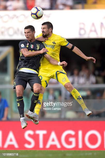 Cristiano Ronaldo of Juventus FC competes for a header with Nenad Tomovic of AC ChievoVerona during the Serie A football match between AC...