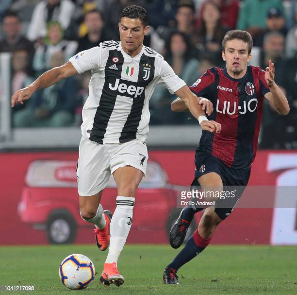 Cristiano Ronaldo of Juventus FC is challenged by Adam Nagy of Bologna FC during the Serie A match between Juventus and Bologna FC at Allianz Stadium...