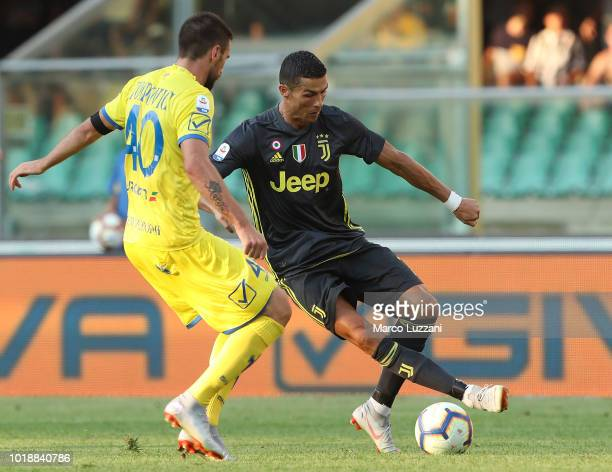 Cristiano Ronaldo of Juventus FC is challenged by Nenad Tomovic of Chievo Verona during the serie A match between Chievo Verona and Juventus at...