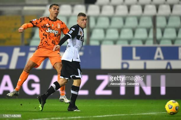 Cristiano Ronaldo of Juventus F.C. Scores their team's third goal under pressure from Simone Iacoponi of Parma Calcio during the Serie A match...