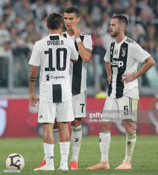 Cristiano Ronaldo of Juventus FC speaks with his teammates Paulo Dybala and Miralem Pjanic during the Serie A match between Juventus and Genoa CFC at...