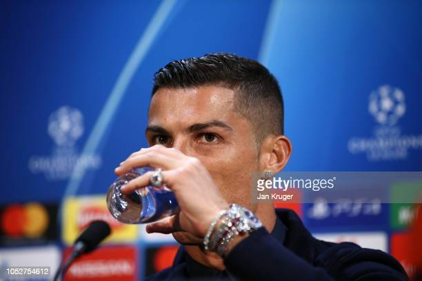 Cristiano Ronaldo of Juventus has a drink during a press conference ahead of their UEFA Champions League Group H match against Manchester United at...