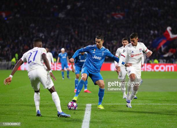 Cristiano Ronaldo of Juventus holds off the Lyon defence during the UEFA Champions League round of 16 first leg match between Olympique Lyon and...