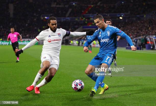 Cristiano Ronaldo of Juventus is challenged by Jason Denayer of Olympique Lyon during the UEFA Champions League round of 16 first leg match between...