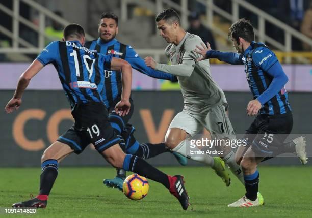 Cristiano Ronaldo of Juventus is challenged by Marten De Roon and Berat Djimsiti of Atalanta BC during the Coppa Italia match between Atalanta BC and...