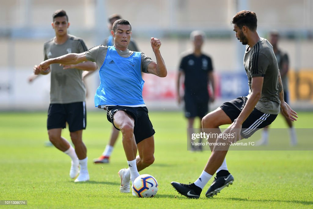 Cristiano Ronaldo (L) of Juventus is challenged during a training session at JTC on August 5, 2018 in Turin, Italy.